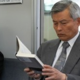 Father reading book on train