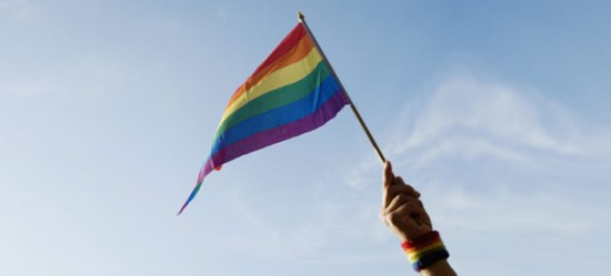 Hand waving gay pride rainbow flag
