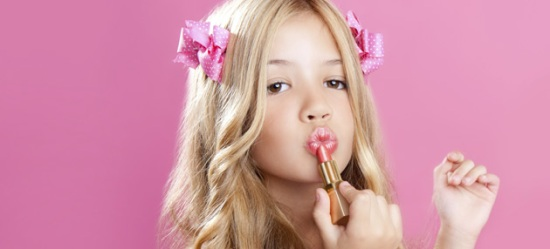 Young girl applying lipstick