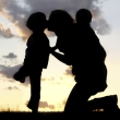 Mother embracing two young children in silhouette
