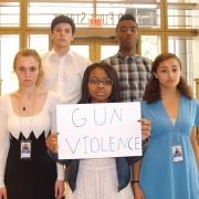 5 teens holding up gun violence sign
