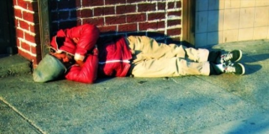 Homeless man sleeping on the sidewalk