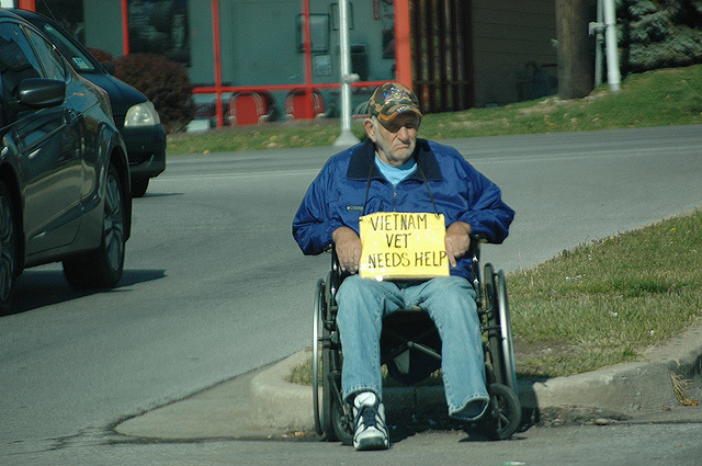 Homeless and disabled Vietnam veteran panhandles on the street