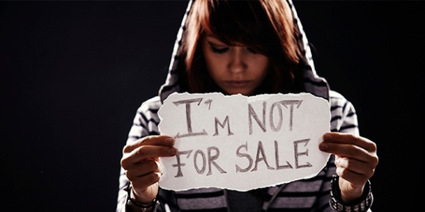 "Teen girl holding ""I'm not for sale"" sign"
