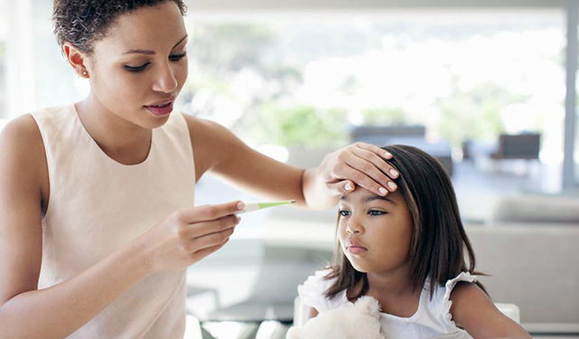 Mother feeling forehead of her daughter