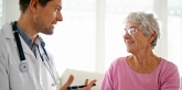 Smiling older woman chatting with doctor