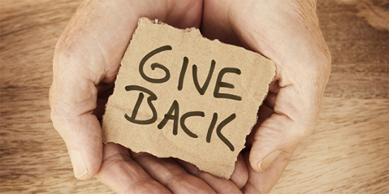 """Hands holding a sign saying """"give back"""""""