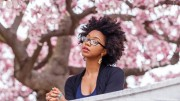 Professional black woman under cherry blossoms