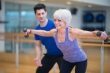 A personal trainer is teaching a senior adult woman how to lift weights at the gym.
