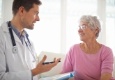 A smiling senior woman chatting with her GP during an appointment