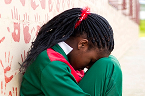 A young school girl leans against a wall covered in painted hands, her head in her lap.