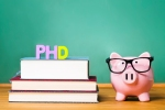 PhD degree theme with textbooks and piggy bank with glasses on green chalkboard background