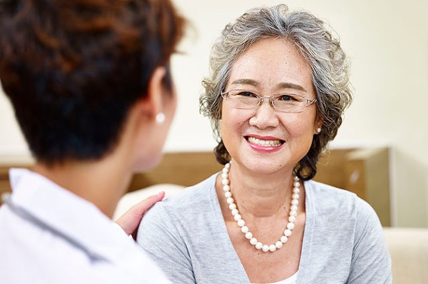 senior asian woman talking to family doctor