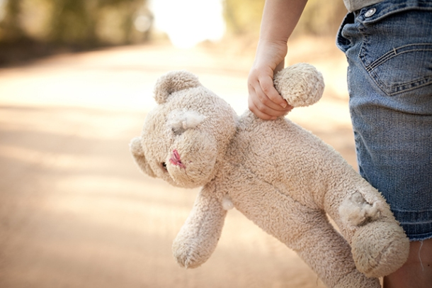 Runaway or Lost Girl Holding Old, Ragged Teddy Bear