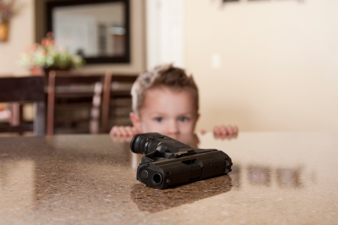A small child staring at a hand gun within reach on a table