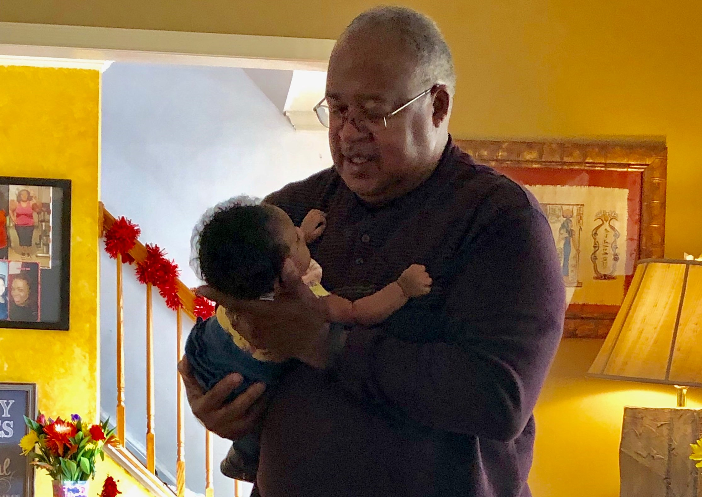 African American grandfather cradling granddaughter
